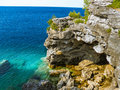 Rocky grotto over turqoise blue water the of the lake Royalty Free Stock Photography