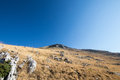 Rocky mountain with yellow grass fields and blue sky in the back Royalty Free Stock Photo