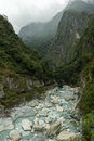 Rocky river between steep and lush mountains in a gorge misty at the taroko national park in taiwan Stock Photography