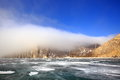 Rocky shore of lake Baikal in the fog in winter Royalty Free Stock Photo