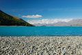 The rocky shore of lake tekapo new zealand and blue water Royalty Free Stock Image