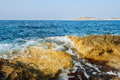 Rocky shoreline of armier the in the north malta with the white tower just visible on the horizon Royalty Free Stock Image