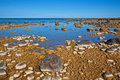 Rocky shoreline a vivid blue and earth brown landscape Royalty Free Stock Image