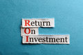 Roi abbreviation acronym on blue paper return on investment Royalty Free Stock Images