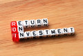 Roi return on investment wood written dices wooden background Royalty Free Stock Photos