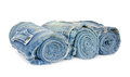 Roll blue denim jeans arranged on white background Royalty Free Stock Photo