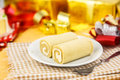 Roll cake on dish against giftboxes Royalty Free Stock Images