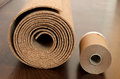 Roll of cork with painting edging tape lies on a brown floor the foor is made pine and covered semimatt lacquer Royalty Free Stock Images