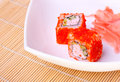 Roll with flying fish roe on a white plate Royalty Free Stock Photography