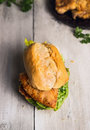 Roll with fried schnitzel and salad leaves on old wooden background german food tradition Stock Image