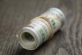 Roll of hundred dollar bills on wooden table shallow dof Stock Photos