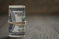Roll of old style hundred dollar bills stand on wooden table shallow dof Royalty Free Stock Photos