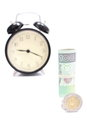Roll of tied banknotes and coins with retro styled alarm clock polish in background time is money concept Stock Images