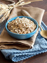 Rolled oats in a bowl blue on napkin with spikes and spoon Stock Image