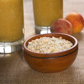 Rolled oats bowl full of with peaches and glasses of fruit milkshakes mixed with oatmeal in the back photographed with natural Stock Photo