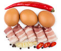 Rolled pieces of bacon pepper garlic and chicken eggs isolated on white background top view Stock Photography