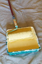 Roller brush with handle in plastic paint tray painter yellow emulsion Royalty Free Stock Photos