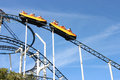 Roller coaster. Minecart with passengers slides down the rails. Royalty Free Stock Photo