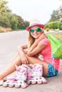 Roller skating teen girl sitting with roller skating shoes teenager is inline skates bag and listening music headphone happy Royalty Free Stock Photo