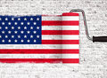 Roller to paint on white brick wall with American USA flag, wall with dripping paint Royalty Free Stock Photo