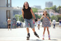 Rollerskating father with his small daughter in city street Royalty Free Stock Photos