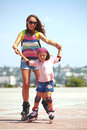 Rollerskating young mother with her years old daughter in park Stock Photography