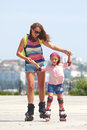 Rollerskating young mother with her years old daughter in park Stock Images