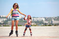 Rollerskating young mother with her years old daughter in park Royalty Free Stock Photos