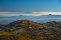 Rolling hills and mountains at autumn sunny day with fog, view from Zeljin mountain Royalty Free Stock Photo