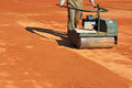 Rolling a tennis court worker with roller editing clay Stock Image