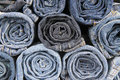 Rolls of different worn blue jeans stacked Stock Photography