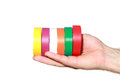 Rolls of rainbow color insulation adhesive tape on the electrician hand isolated on a white background Royalty Free Stock Images
