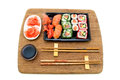 Rolls and sushi on a bamboo board isolated on white background Royalty Free Stock Photo