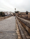 Roman bridge of emerita augusta view the behind some houses are located in the spanish city merida on a cloudy day in the Stock Photo