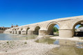 Roman bridge and guadalquivir river in cordoba andalusia spain over blue bright sky Stock Photos