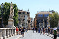 Roman bridge over the tiber river with pedestrians as seen from castle st angelo Royalty Free Stock Photos