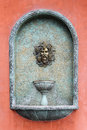 Roman head fountain vintage on red wall Royalty Free Stock Image