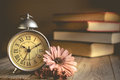 Roman Numeral in Vintage Alarm Clock and Stack of Book Background Royalty Free Stock Photo