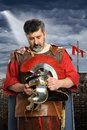 Roman soldier praying portrait of while holding helmet Royalty Free Stock Images