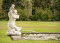Roman style fountain old statue in a garden Stock Image