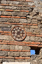 Roman wall decoration ancient sun shaped ceramic mounted on a to mark a cross roads in a town Stock Photos