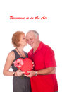 Romance is in the air an elderly couple embracing after husband gave wife flowers and chocolates Stock Photo