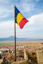 Romania flag at the medieval fortress in rasnov romanian on hill transylvania and town background Stock Photography