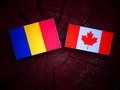 Romanian flag with Canadian flag on a tree stump isolated