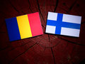 Romanian flag with Finnish flag on a tree stump isolated