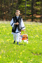 Romanian national port young boy dressed in carrying a traditional basket on the beautiful green grass and full of dandelions Stock Photo