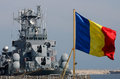 Romanian warship in port with romania flag in front Royalty Free Stock Photos