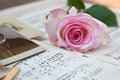 Romantic arrangement with a pink rose on old sheets of music and old photographs Stock Image