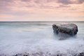 Romantic atmosphere in peaceful morning at sea. Big boulders sticking out from smooth wavy sea. Pink horizon Royalty Free Stock Photo