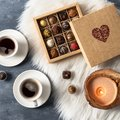 Romantic atmosphere two cups of coffee, chocolate candies and candles. Happy Valentines Day. Top view